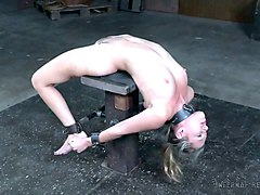 white lady restrained and arched on the small wooden post