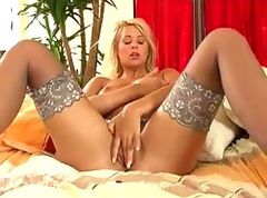 Busty blonde in stockings fingers her shaved pussy