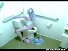 a kinky floozy is touching her self while sitting on a toilet and voyeur is spying on her
